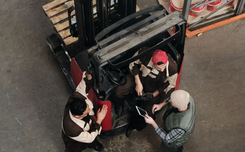 Title image for Group Health Insurance Plans showing a man in a pallet stacker sitting and talking to two other men.