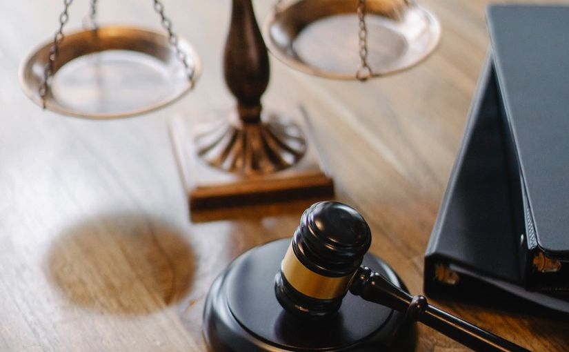 Title image for Civil Penalty Amounts for 2021 Increased by DOL [VIDEO] showing a gavel and a scale of justice on top of a desk.