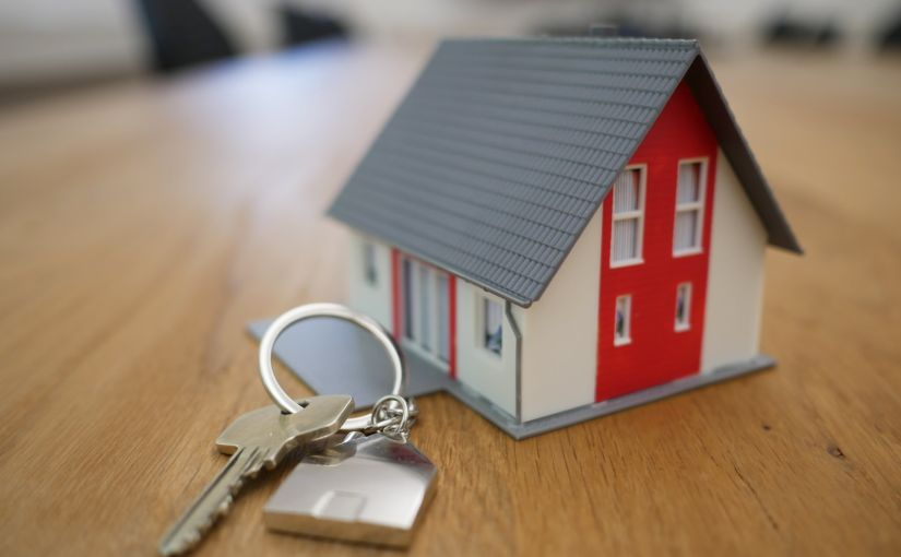 Title image for How to Insure a Second Home showing a small toy house and a key and keychain on top of a table.