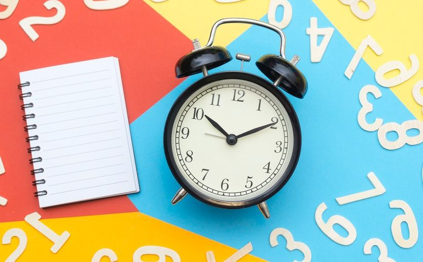 Title image for ACA Reporting Requirements for 2020 showing a clock, a notebook and number figures laying on top of a colorful surface.