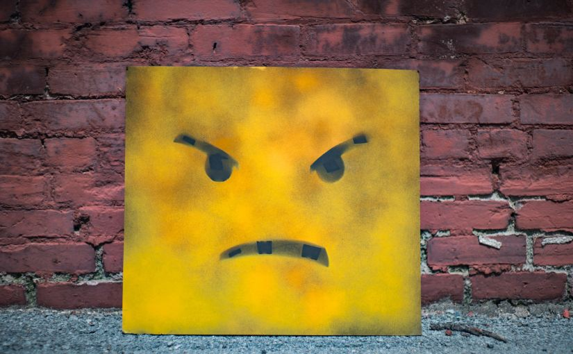 Title image for Why You Need Bailee Coverage showing the expression of an angry face painted on a metal sign resting against a brick wall.