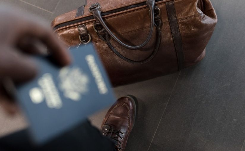 Title image for What is Travel Insurance showing a person standing next to a traveling bag and holding a passport.