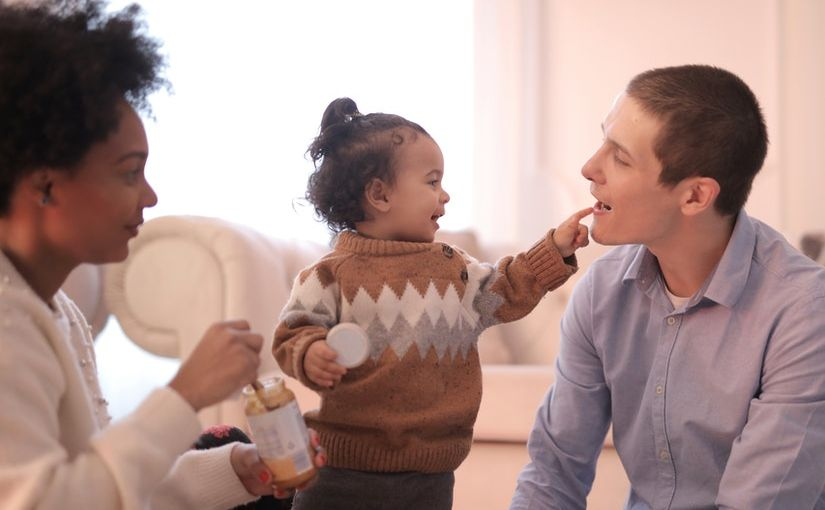 Title image for Employers That Offer Adoption Benefits showing two parents feeding and spending time with their daughter.