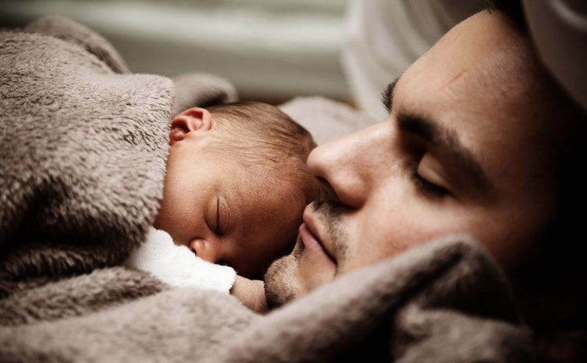 Title image for Paid Paternity Leave showing a father holding his newborn baby.
