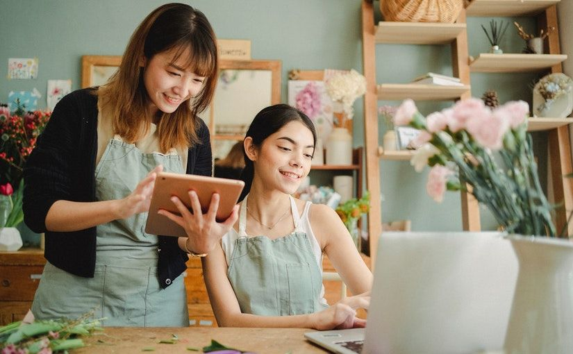 Title image for How to Manage a Bilingual Workplace showing two workers of different ethnicities using electronic devices inside a flower shop.