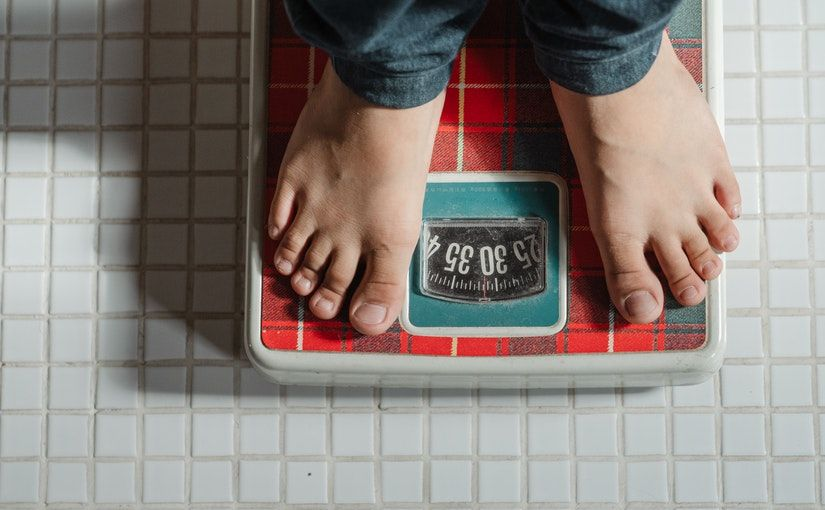 Title image for New AMA Obesity Classification Can Impact Your Bottom Line showing a person measuring his weight by standing on a bathroom scale.