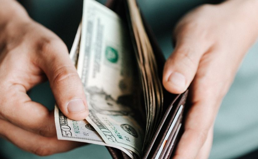 Title image for Top 4 Reasons For Not Paying Workers' Compensation Claims Out of Pocket showing a person taking money out of his wallet.
