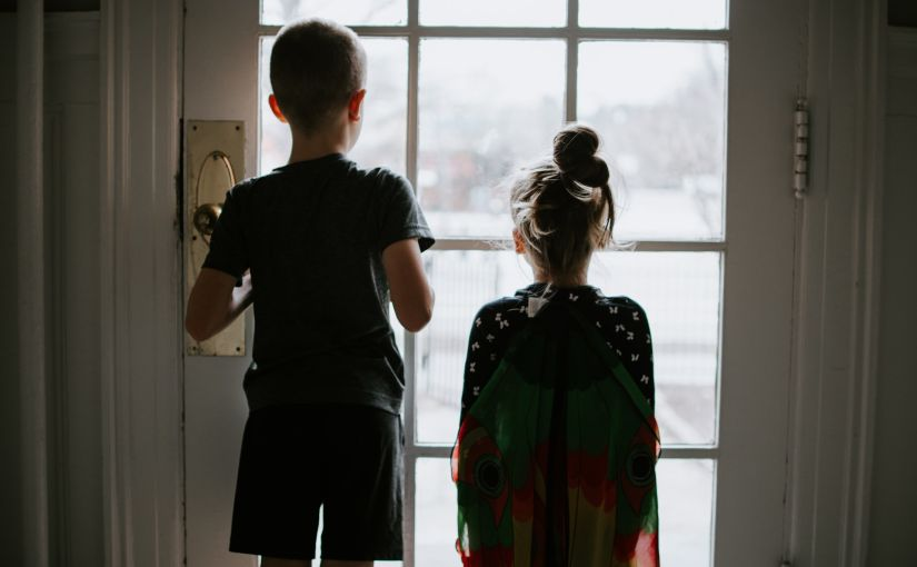 Title image for Is Home Invasion Insurance Really Necessary showing two young children inside a home looking out through the front-door window.