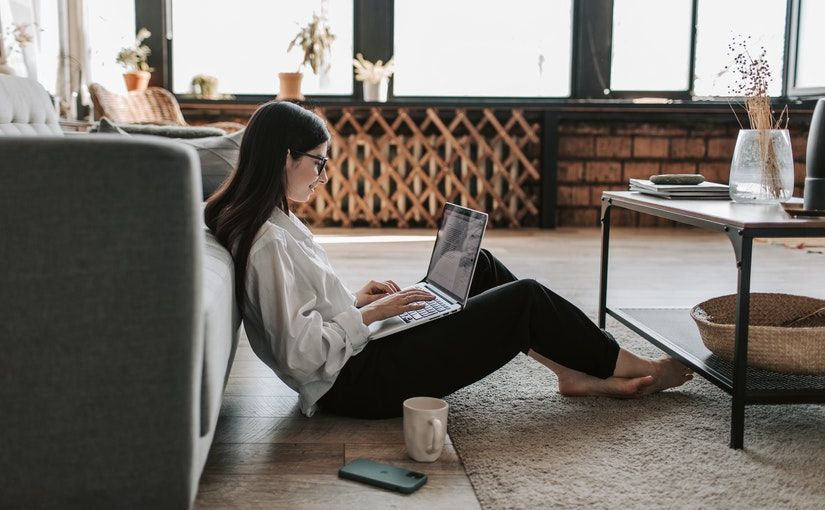 Title image for Telecommuting Pros and Cons showing a woman working from home on a laptop while resting on the sofa.