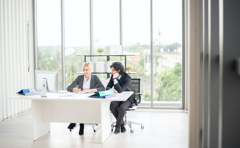 Title image for Training for Employees Supervisors and Managers showing a supervisor training a new employee in an office space.