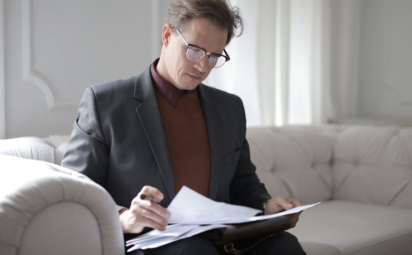 Title image for California Employer Records Recordkeeping Requirements showing an employer reviewing documents while sitting on a sofa in his office.