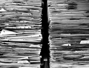 Title image for California Employer Records and Recordkeeping Requirements showing two tall stacks of paper documents.