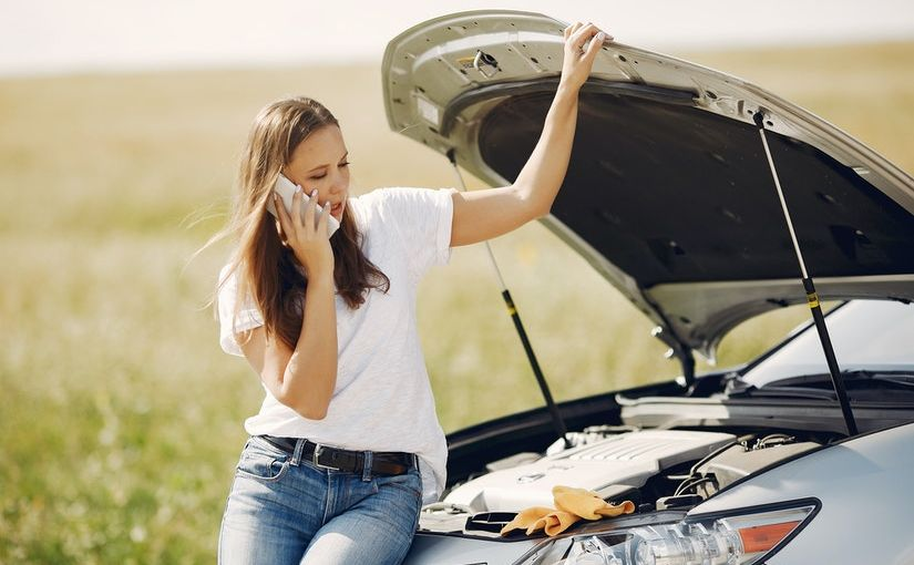 Title image for What is the Difference between Uninsured Motorist and Underinsured Motorist Coverage? showing a woman stranded on the side of the road with her car's hood open and she's making a call.